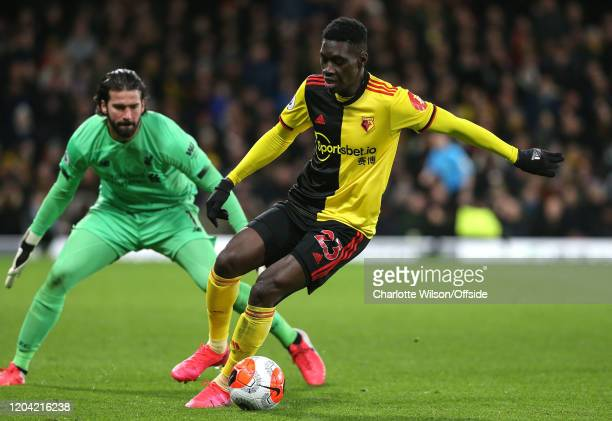 Liverpool goalkeeper Alisson Becker pressures Ismaila Sarr of Watford during the Premier League match between Watford FC and Liverpool FC at Vicarage...