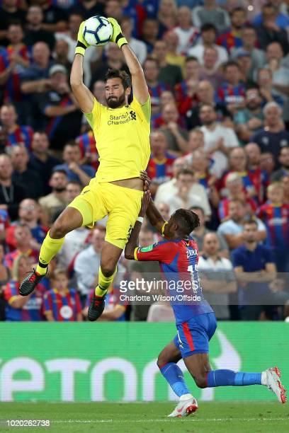 Liverpool goalkeeper Alisson leaps up to catch the ball as Wilfried Zaha of Palace closes in during the Premier League match between Crystal Palace...