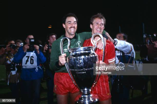 Liverpool goalkeeper Bruce Grobbelaar and teammate Phil Neal celebrate with the European Cup after Liverpool beat Roma 42 on penalties in the...