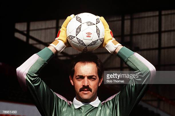 Liverpool goalkeeper Bruce Grobbelaar holds a ball above his head as he poses for the camera