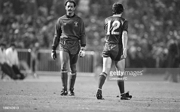 Liverpool goalkeeper Bruce Grobbelaar walks past Liverpool's Steve Nicol looking pensive as he prepares to face the first Roma spot kick from...