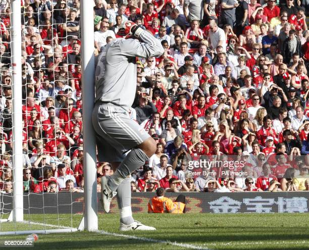 Liverpool goalkeeper Jose Reina stands dejected after Arsenal's Marouane Chamakh's shot hit the post and bounced of Reina for Arsenal's first goal...