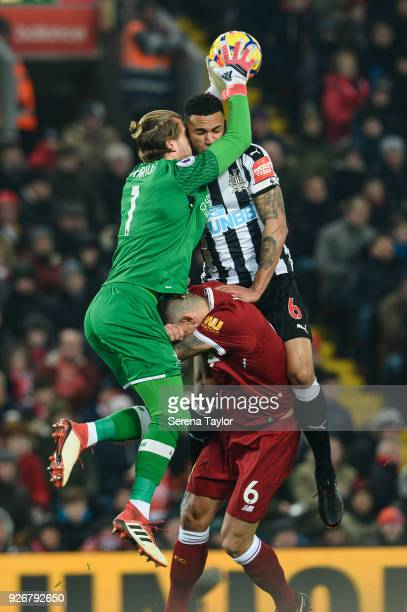 Liverpool Goalkeeper Loris Karius catches the ball over a challenging Jamaal Lascelles of Newcastle United during the Premier League Match between...