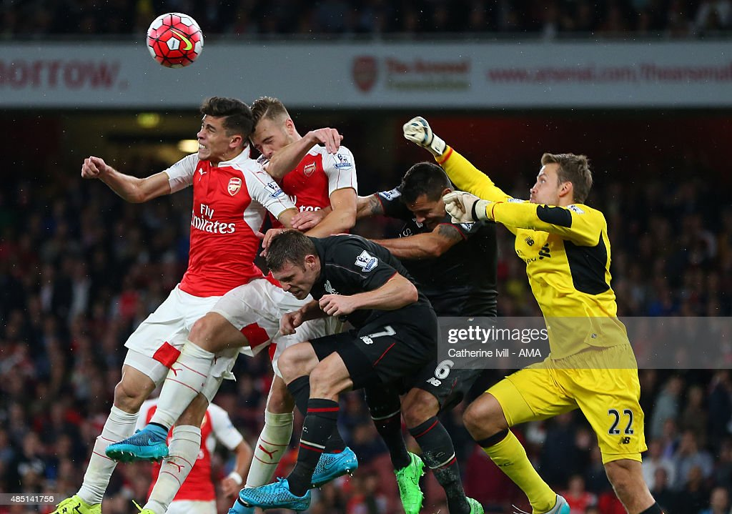 Liverpool goalkeeper Simon Mignolet punches away a last minute shot as he gets caught up with Gabriel Paulista, Calum Chambers of Arsenal along with James Milner and Dejan Lovren of Liverpool during the Barclays Premier League match between Arsenal and Liverpool at the Emirates Stadium on August 24, 2015 in London, United Kingdom.