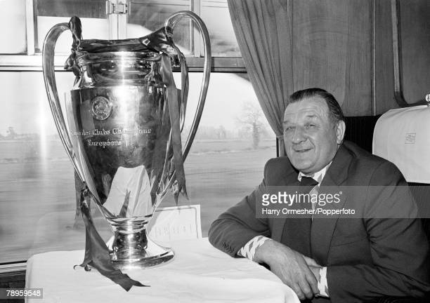 Liverpool manager Bob Paisley posing with the European Cup trophy on the train back to Liverpool the day after his team had retained the trophy with...
