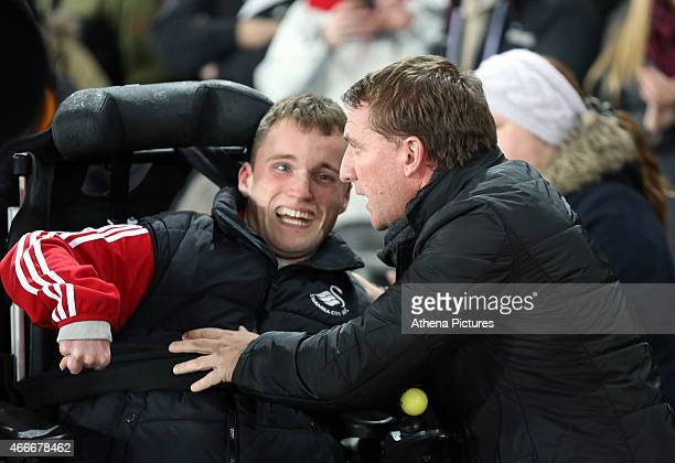 Liverpool manager Brendan Rodgers greets a young disabled Swansea fan prior to the Premier League match between Swansea City and Liverpool at the...