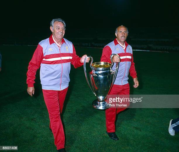 Liverpool manager Joe Fagan and his assistant Ronnie Moran proudly carry the trophy after Liverpool had beaten AS Roma in the European Cup Final at...