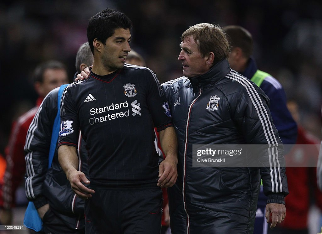 Liverpool manager Kenny Dalglish congratulates his double goal scorer Luis Suarez at end of the match during the Carling Cup Fourth Round match between Stoke City and Liverpool at Britannia Stadium on October 26, 2011 in Stoke on Trent, England.
