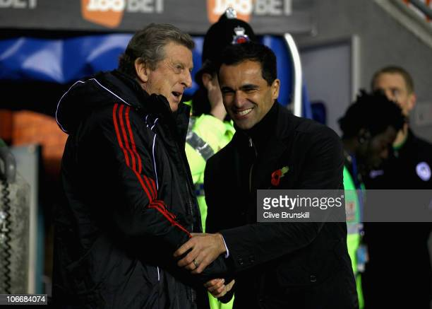 Liverpool manager Roy Hodgson shares a joke with Wigan Manager Roberto Martinez during the Barclays Premier League match between Wigan Athletic and...