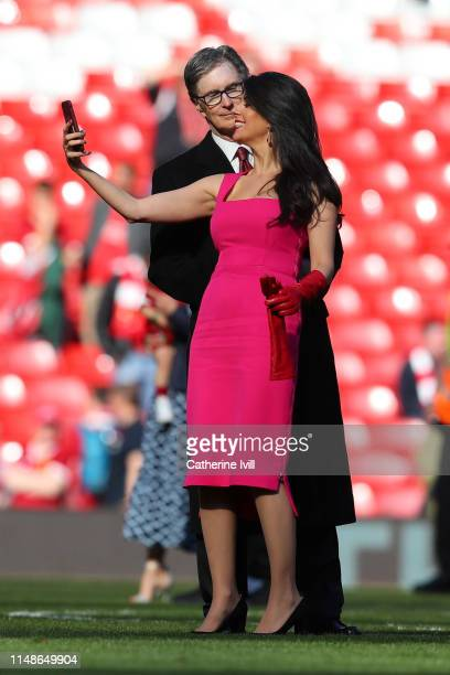 Liverpool owner John W Henry and his wife Linda Pizzuti take a selfie on the pitch after the Premier League match between Liverpool FC and...