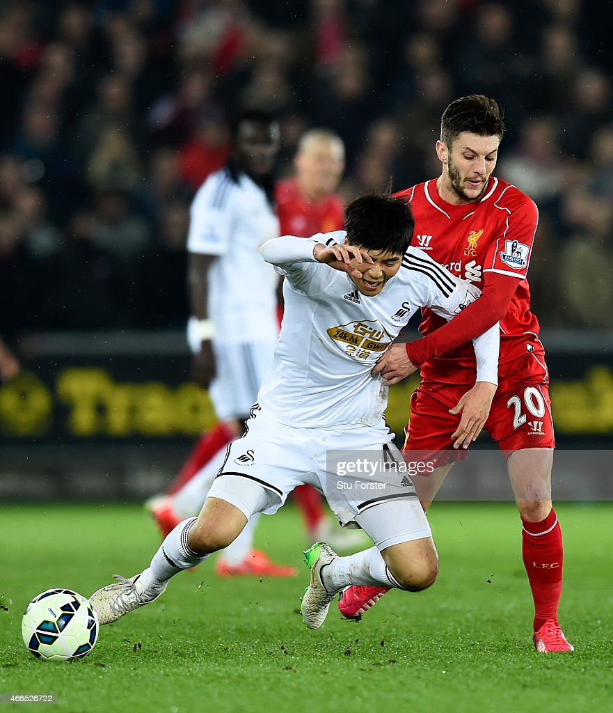 Liverpool player Adam Lallana (r) challenges Ki Sung - Yueng during the Barclays Premiership match between Swansea City and Liverpool at Liberty Stadium on March 16, 2015 in Swansea, Wales.