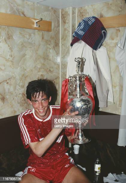 Liverpool player Gary Ablett celebrates In the dressing room with the First Divison Trophy after winning the 1989/90 First Division Championship...