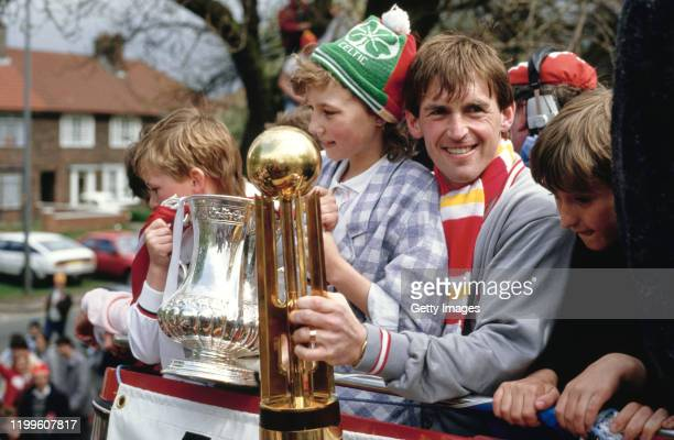Liverpool player manager Kenny Dalglish celebrates with the trophies on the teams homecoming bus parade after completing the Football League and FA...