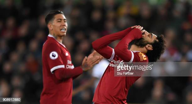 Liverpool player Mohamed Salah reacts after missing a chance as Roberto Firmino looks on during the Premier League match between Swansea City and...