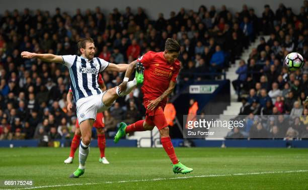 Liverpool player Roberto Firmino scores the firstr goal with a header despite the challenge of West Brom defender Gareth McAuley during the Premier...
