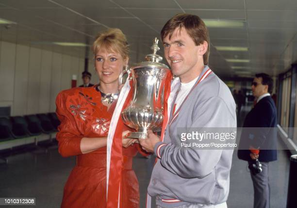 Liverpool playermanager Kenny Dalglish and his wife Marina holding the trophy at Liverpool Airport having flown back from London after victory in the...
