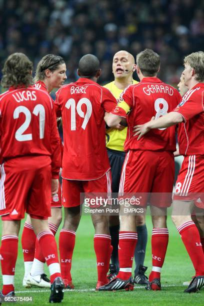 Liverpool players argue with referee Tom Henning Ovrebo
