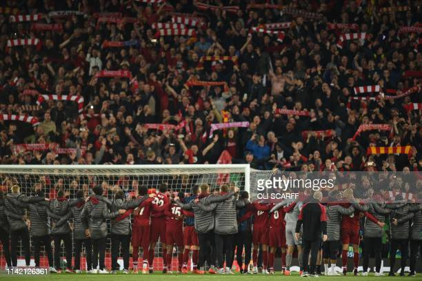 Liverpool players celebrate in front of the Kop after winning the UEFA Champions league semifinal second leg football match between Liverpool and...