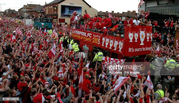 Liverpool players celebrate on an opentop bus during the victory parade as they pass the Kop end at Anfield