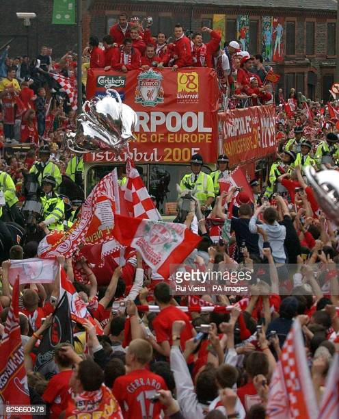 Liverpool players celebrate on an opentop bus during the victory parade at Anfield