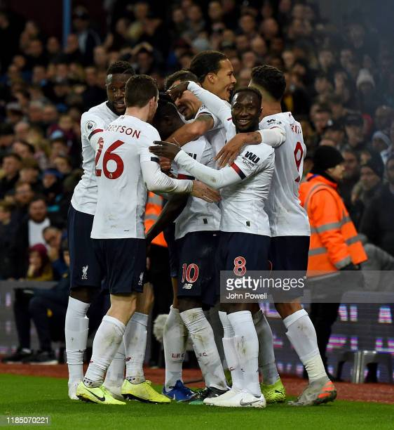 Liverpool players celebrate with goal scorer Sadio Mane after he scores the winning goal during the Premier League match between Aston Villa and...