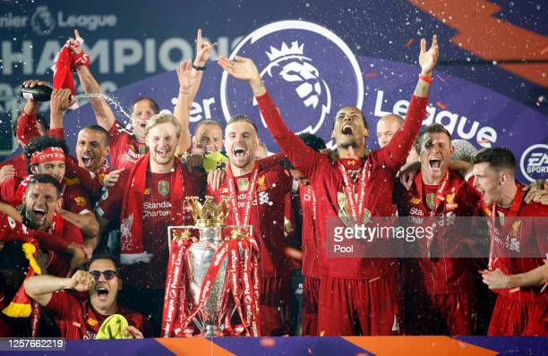 Liverpool players celebrate with The Premier League trophy following the Premier League match between Liverpool FC and Chelsea FC at Anfield on July...