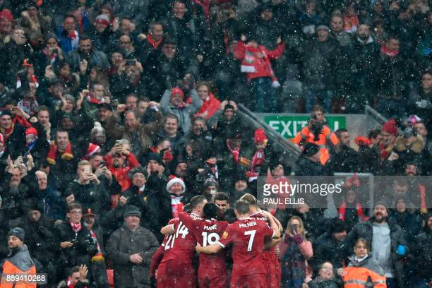 Liverpool players crowd around Liverpool's Egyptian midfielder Mohamed Salah after Salah scored the opening goal during the English Premier League...
