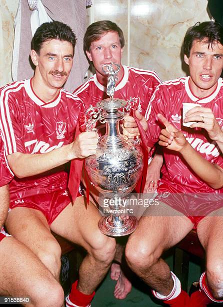 Liverpool players Ian Rush Ronnie Whelan and captain Alan Hansen celebrate winning the league title with the trophy in the dressing room after the...