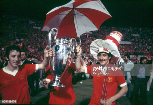 Liverpool players Jimmy Case and Terry McDermott celebrate with the trophy after their victory over Borussia Moenchengladbach in the European Cup...