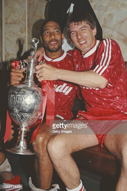 Liverpool players John Barnes and Peter Beardsley celebrate in the dressing room with the First Divison Trophy after winning the 1989/90 First...