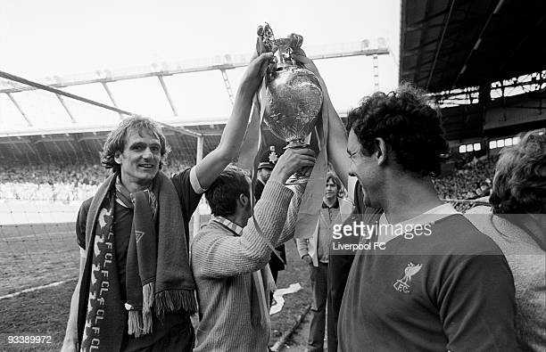 Liverpool players Phil Thompson and Ray Kennedy hold the Football League Division One trophy as they are joined by a fan after the Football League...