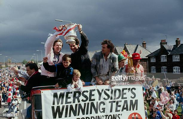 Liverpool players Ronnie Whelan and Jim Beglin celebrate being the FA Cup and Canon League Division One champions and parade the trophies during a...