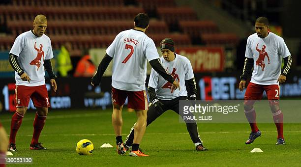 Liverpool players warm up wearing a t-shirt supporting team-mate Luis Suarez before the English Premier League football match between Wigan Athletic...