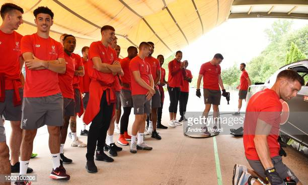 Liverpool players watch as James Milner of Liverpool changing tyres during a tour of Roush Fenway Racing on July 21 2018 in Charlotte North Carolina