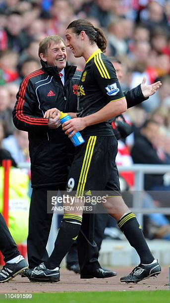 Liverpool 's Scottish manager Kenny Dalglish greets Liverpool's English forward Andy Carroll after he was substituted during the English Premier...