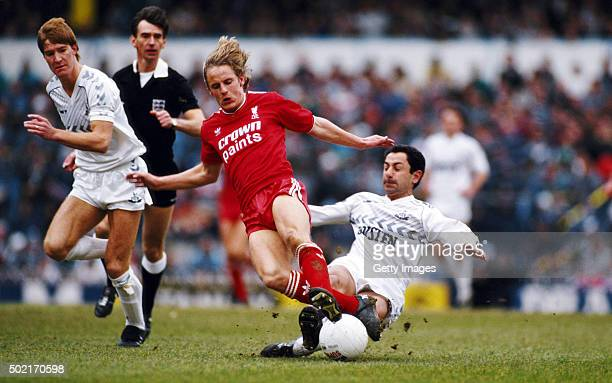 Liverpool striker Paul Walsh is tackled from behind by Spurs player Ossie Ardiles as defender Richard Gough looks on during the First Divison match...
