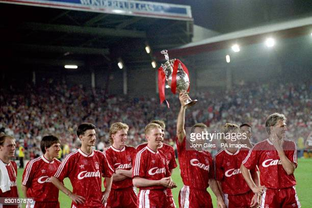 Liverpool striker Ronny Rosenthal holds aloft one of the two league championship trophies at Anfield, after his side defeated Derby County 1-0, as he...