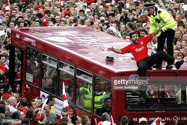 Liverpool supporter jokes around with a police man after asked to remove himself from the bus during the Liverpool homecoming Victory Street Parade...