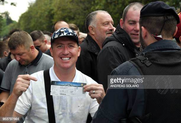 A Liverpool supporter shows his match ticket as police officials look on in Rome on May 2 ahead of the Champions League semifinal football match AS...