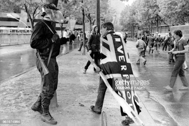 A Liverpool supporter wrapped in a Union flag walks past police forces who are attempting to prevent Liverpool supporters from entering the Parc des...