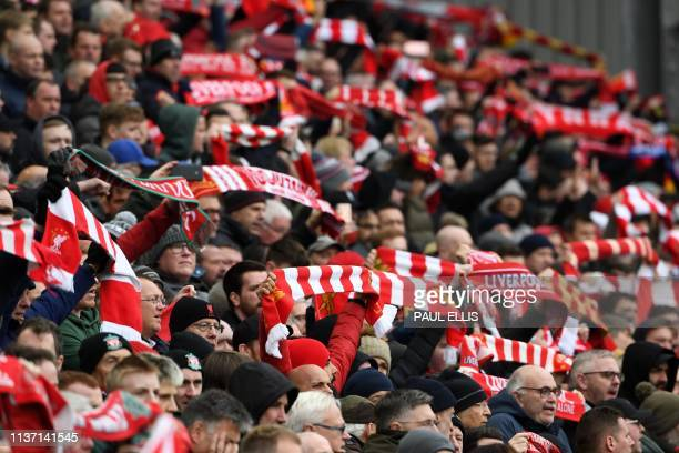 Liverpool supporters hold up their scarves in the crowd ahead of the English Premier League football match between Liverpool and Chelsea at Anfield...