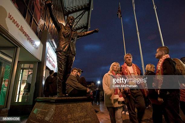 Liverpool supporters sitting below the statue of former manager Bill Shankly outside Anfield before their team's Carling Cup third round tie at home...