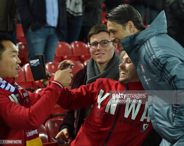 Liverpool supporters take a picture with Bayern Munich's Croatian head c oach Niko Kovac prior the UEFA Champions League round of 16 first leg...