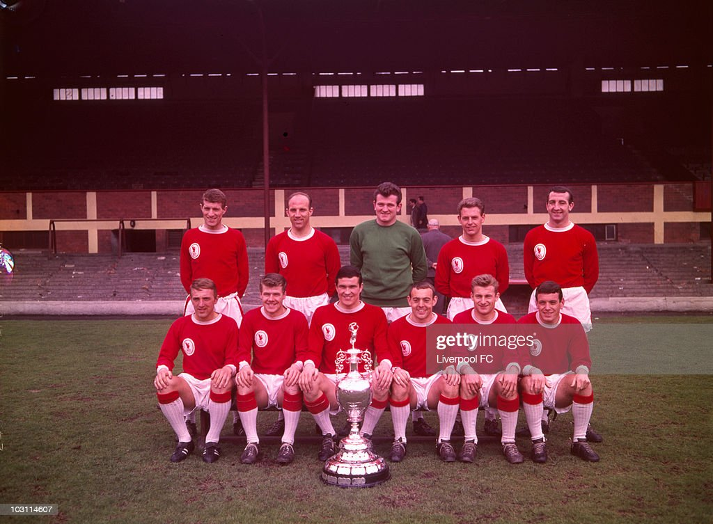 Liverpool team group.... Back Row (from left to right) Willie Stevenson, Ronnie Moran, Tommy Lawrence, Gordon Milne and Gerry Byrne... Front Row (from left to right) Peter Thompson, Alf Arrowsmith, Ron Yeats, Ian St. John, Roger Hunt and Ian Callaghan pose in front of the main stand at Anfield celebrating being crowned the League Division One Champions during a photoshoot held on May 30, 1964 at Anfield, in Liverpool, England. Liverpool were crowned league champions of League Division One for 1963/64 season with 57 points finishing 4 points ahead of Manchester United in 2nd place.
