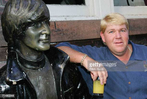 American golfer John Daly is pictured leaning on the statue of former Beatle John Lennon before playing the guitar at the Cavern Club in Liverpool 18...