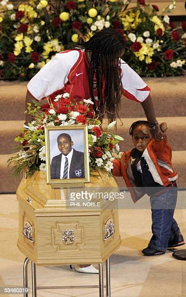 An unidentified sister of murdered teenager Anthony Walker helps a younger family member back to his seat after laying gifts at the altar during his...
