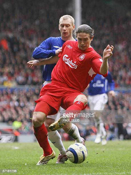 Liverpool, UNITED KINGDOM: Liverpool's Harry Kewell keeps the ball from Everton's Tony Hibbert during their English Premiership soccer match at...