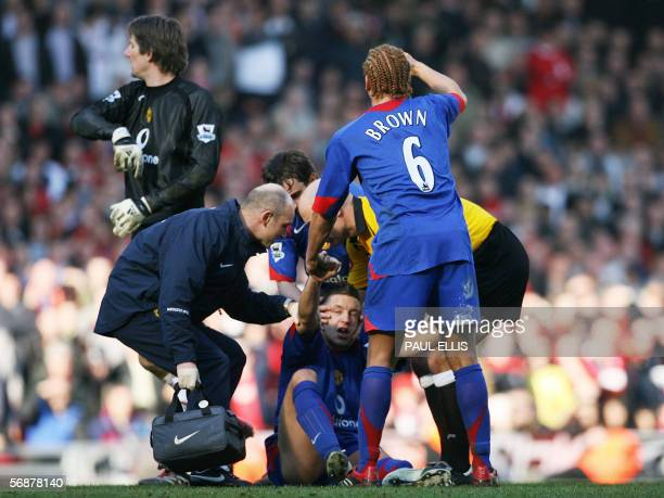 Manchester United striker Alan Smith is lowered to the ground after breaking his leg during the English FA Cup soccer match against Liverpool 18...