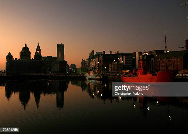Liverpool's Albert Dock sits against the backdrop of the setting sun and The Liver Building on February 17 Liverpool England The historic dock yard...