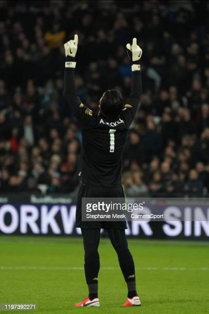 Liverpool's Alisson Becker celebrates his side's first goal during the Premier League match between West Ham United and Liverpool FC at London...